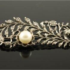 Zilveren broche met 14 karaat gouden accenten en briljant.